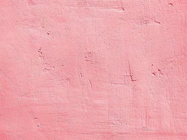 ピンクの漆喰コンクリート壁のテクスチャ、汚れた不均一な塗装石膏の構築された構造を塗装。