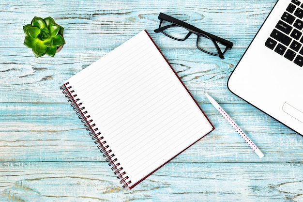 ラップトップ、ノートブック、ペン、リモートワーク用のアクセサリー、メガネ、ツール、小さな緑の花のある職場