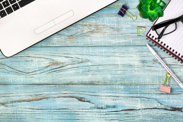 職場、ラップトップ、ノートブック、ペン、メガネ、青い木製のテーブルの上にあるリモート作業用のツール。