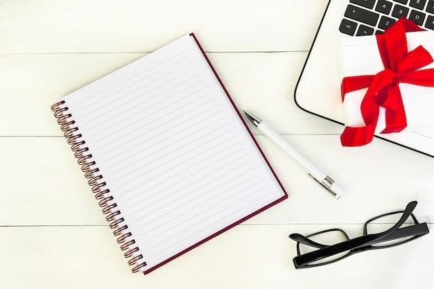ノートパソコンのキーボード、ノートブック、白い木製のテーブルの上にペンと赤い絹のリボンの弓が付いているギフト用の箱の職場