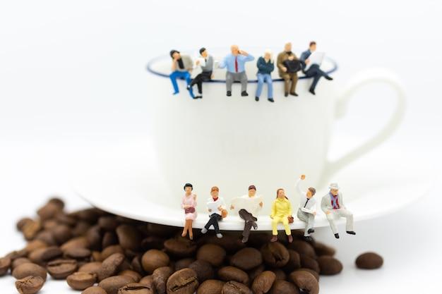 一杯のコーヒーの上に座って、コーヒーブレークを持つビジネスチーム