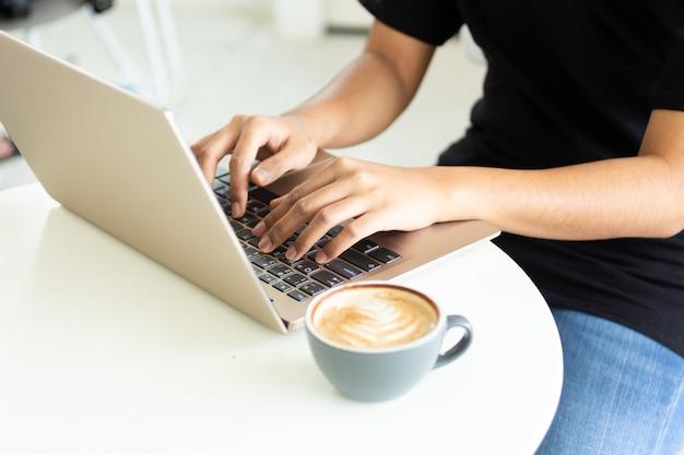 人々はコンピューターを使って仕事をし、コーヒーを飲みます