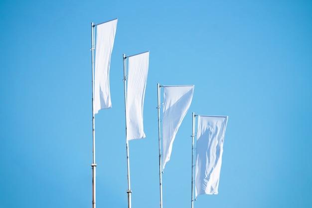マストに掛かっている青い空を背景に白い旗がたくさん