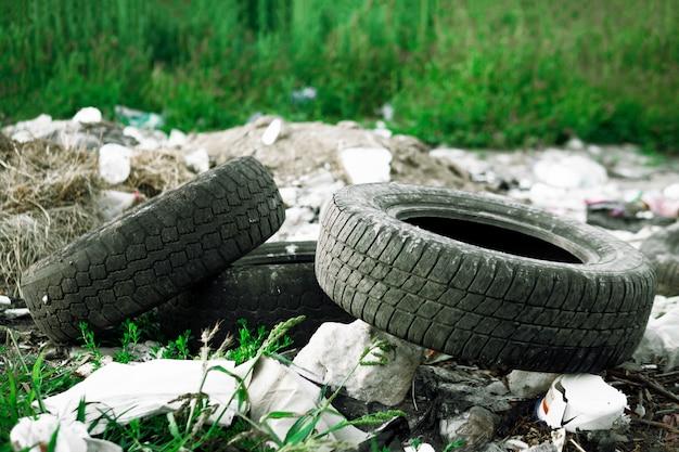 摩耗した車のタイヤはゴミに横たわっています。環境汚染