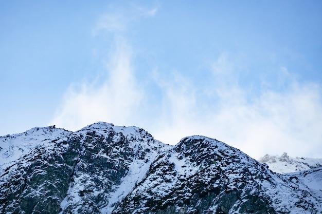 アルプスの雪をかぶった山々。山の頂上近くを飛ぶ雲