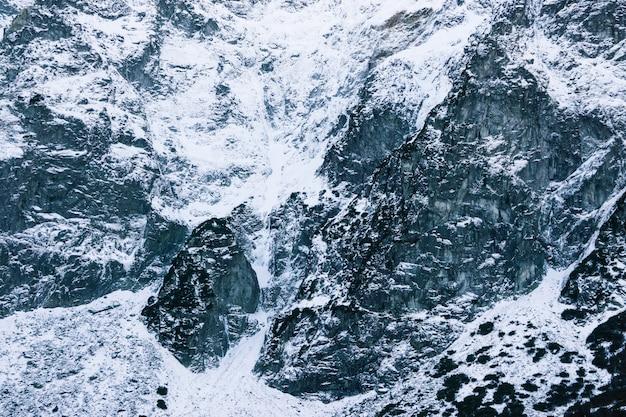 雪をかぶった山のクローズアップ。雪の中の石のテクスチャ