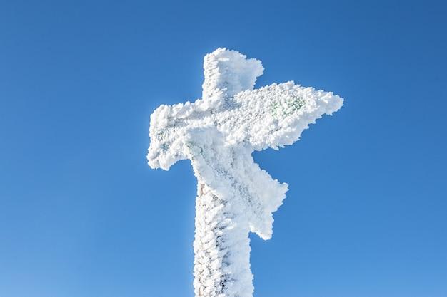 雪に覆われた山の木製の道標。