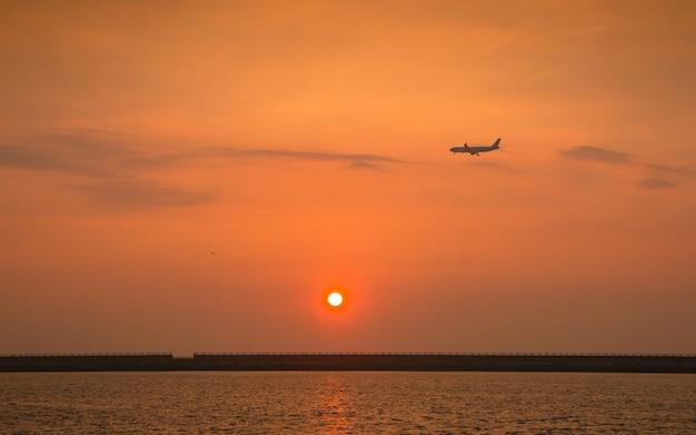 Красивый заход солнца и самолет на острове чеджу делают, южная корея.