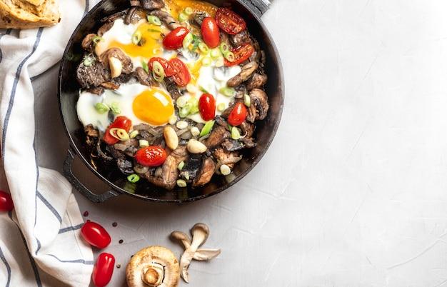マッシュルーム、トマト、玉ねぎと灰色の背景、トップビューでフライパンで目玉焼き