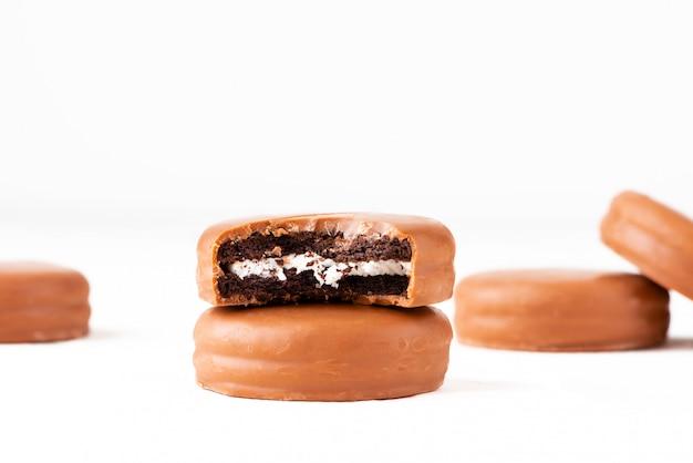 白い背景の上のチョコレート艶出しのチョコレートビスケットサンドイッチ。