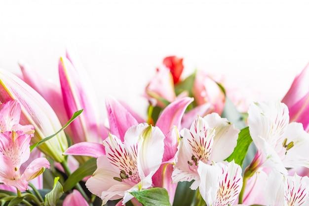 白いアルストロメリアの花と白地にピンクのユリのクローズアップの花束。テキスト、コピースペースの空き領域を持つ花春の背景。美しい花が咲くと組成。