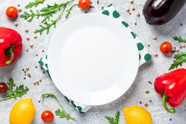 健康食品。野菜、レモン、ひよこ豆、コンクリートのテーブル、トップビューで空の白い皿の周り。ベジタリアンとビーガンフードコンセプトフラットが横たわっていた。