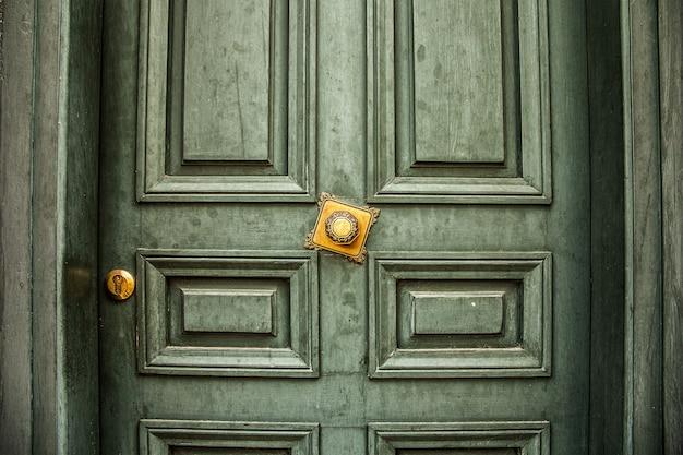 黄金のハンドルが付いている旧式な緑のドア