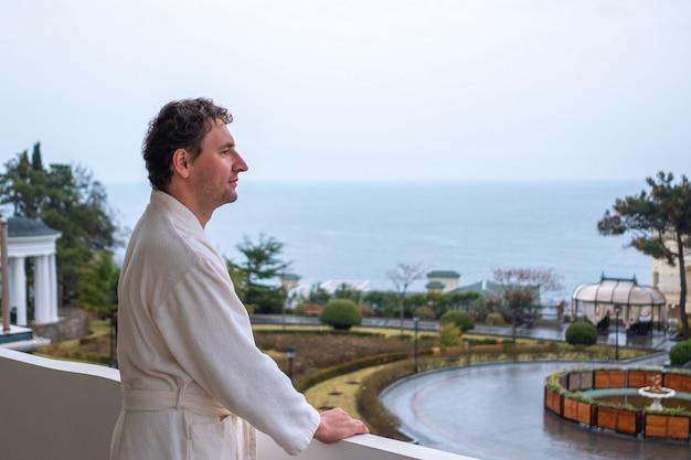 Мужчина в белом халате стоит на балконе резиденции с видом на море