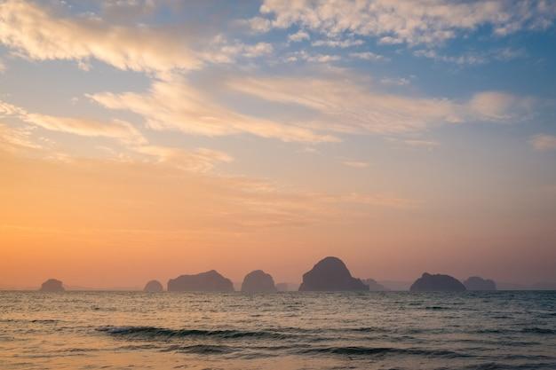 日没時に海から岩の多い島を見る