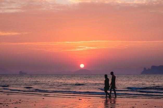 日没の海の風景の人々のシルエット