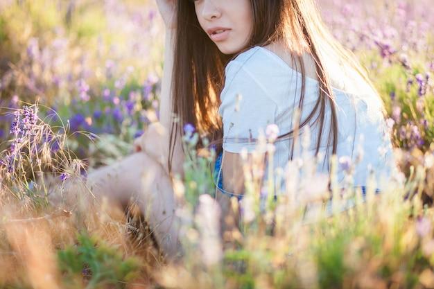 ラベンダーの牧草地に座っている美しい夢の孤独な少女