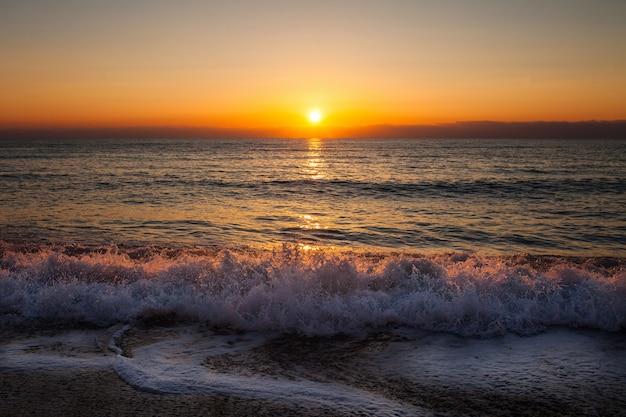 Вечер с заходящим солнцем на пляже с морской прибой