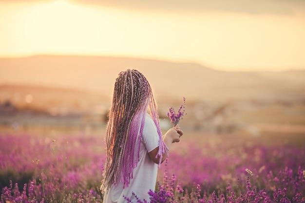 後ろから見た少女がラベンダー畑に花束を集める