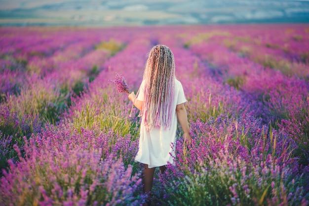 彼女の手に白いドレスとラベンダーの花束を身に着けている彼女の頭に紫の三つ編みを持つ少女