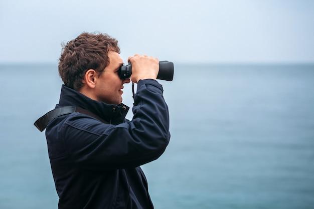 Молодой человек смотрит вдаль в бинокль на фоне моря