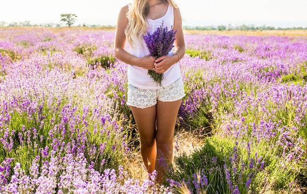 Девушка в белой футболке и шортах с букетом в руках стоит на лавандовом поле