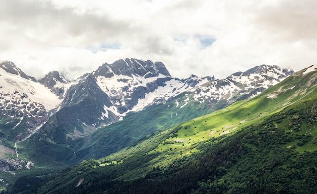 Домбайский хребет на кавказе летом, заснеженные вершины и зеленые горные склоны