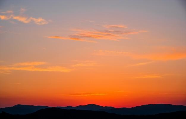 風景、山を背景に空に沈む夕日、日没時に山脈