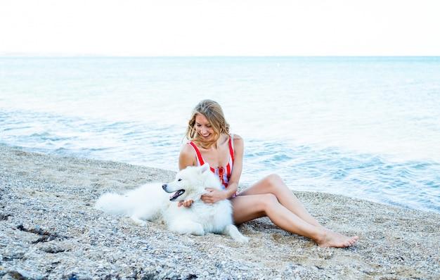 サモエド犬の品種、ビーチで犬と水着の女の子