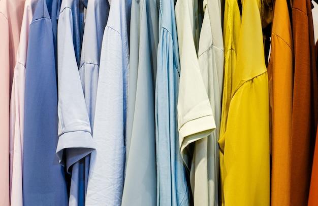 ハンガーにファッショナブルな服。閉じる-店の虹色の服のアップ。店内の衣類の選択。ハンガーにカラフルな服。