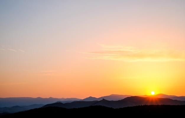 風景、山に対して空に沈む夕日、日没時に山脈