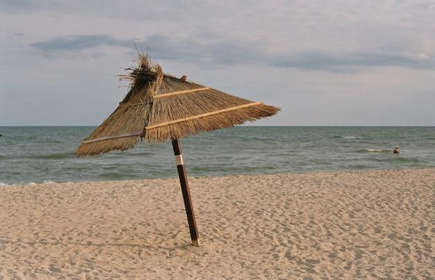 Зонтик на песчаном пляже на фоне моря.