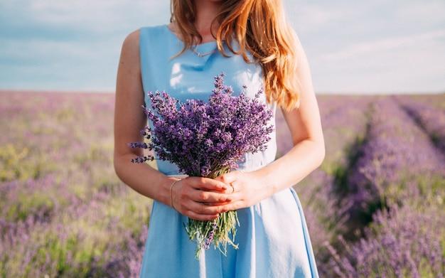 青いドレスの少女の手にラベンダーの花束