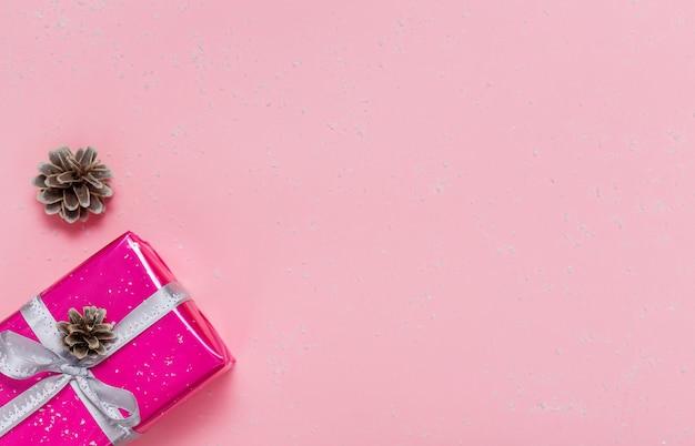 明るいピンクの背景に銀のリボンと小さなピンクのギフトボックス。フラット横たわっていた。コピースペース。