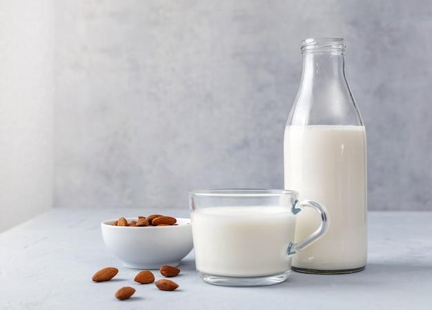 ボトルとアーモンドミルクのカップと灰色のテーブルに生のアーモンド。健康的なコンセプトです。コピースペース。