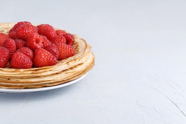 白いプレートに新鮮なラズベリーで飾られた薄いおいしいパンケーキ。閉じる。コピースペース。