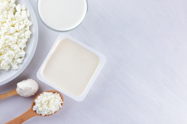 ホワイトボード上の乳製品。カッテージチーズ、クリーム、白い背景の上の柔らかいチーズ