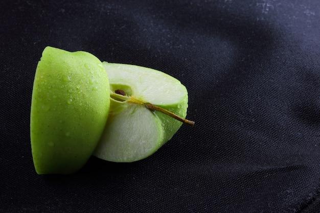 リンゴは暗い所でスライスします。水滴で青リンゴをスライスしました。
