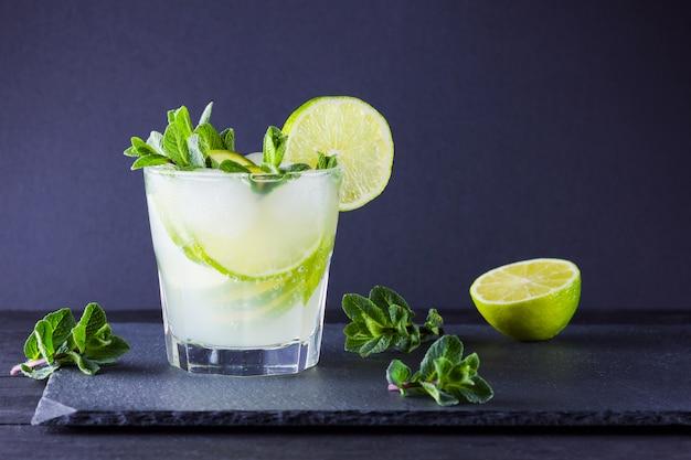 カクテルモヒートとミント。スレートボードにライムと新鮮なミントの爽やかなカクテル。柑橘類と氷の夏の飲み物