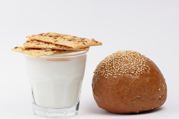 Заквашенный напиток кефир в стакане. кефир и хлеб на белой предпосылке. йогурт и ломтик хлеба