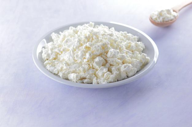 木のスプーンで白い皿にカッテージチーズ。カッテージチーズ。ダイエット用ソフトチーズ。朝食に健康的な乳製品