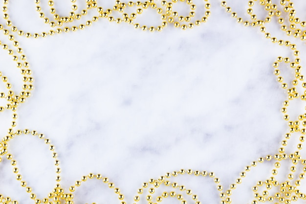 大理石の背景にゴールデンクリスマスビーズ。クリスマスフレーム。白い背景の上の黄金のビーズガーランドのライン。上面図