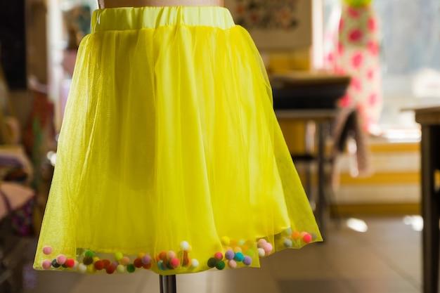 Желтая юбка на манекене. детская юбка с разноцветными шариками.