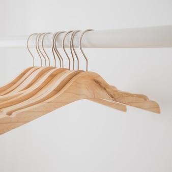木製のハンガーは、オープンクローゼット内の白い清潔で簡単で清潔なライフスタイルのバーに掛かっています。