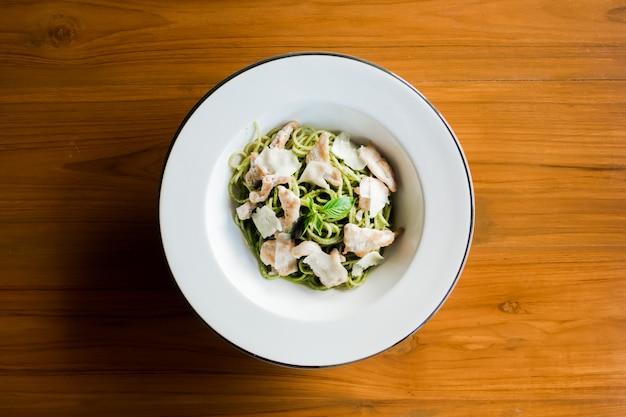ペストソースオリーブオイルとバジルの葉のスパゲッティ。木製のテーブルのトップビュー。
