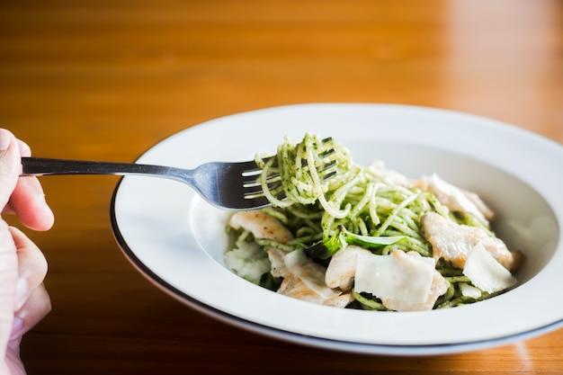 ペストソースオリーブオイルとバジルの葉のスパゲッティ。木製のテーブル。
