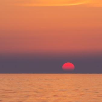 Впечатляющий закат, большая половина солнца спускается к горизонту, на берегу моря вокруг вулкана суволбонг, чеджу, южная корея.