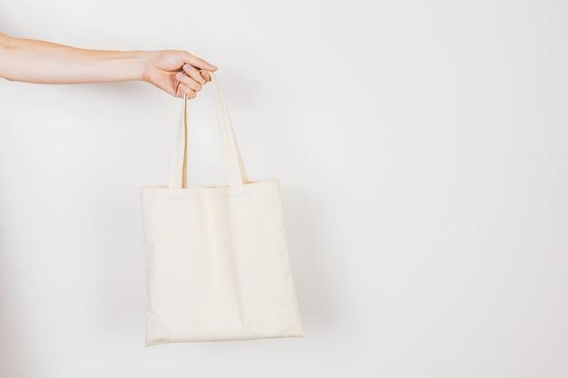 廃棄物ゼロライフスタイルコンセプトの空、きれい、エコフライトートバッグを持っている手。