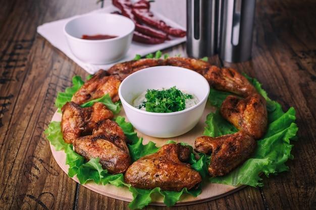 Вкусные куриные крылышки гриль с чесноком и томатным соусом с листьями салата на круглой доске на деревянном деревенском фоне
