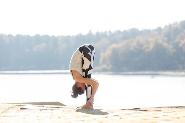 Молодая женщина, занимаясь йогой у озера на открытом воздухе, медитация. занимаешься ли ты спортом? осенний закат.